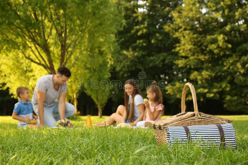 Picnic basket and   on background in park. Picnic basket and happy family on background in park stock photography