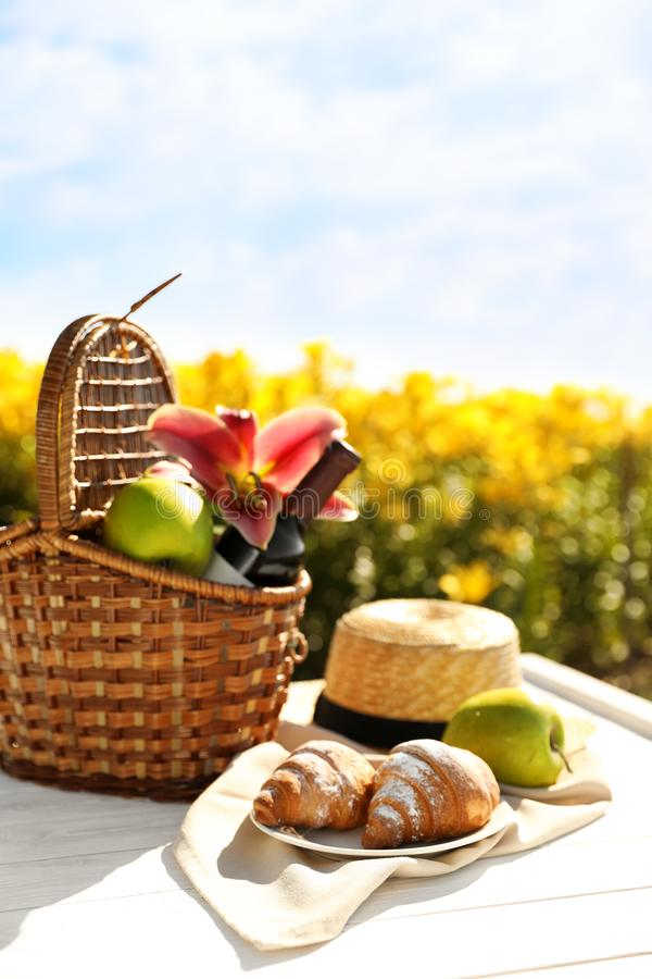 Picnic basket with bottle of wine and food on wte wooden table in lily field. Picnic basket with bottle of wine and food on white wooden table in lily field stock image