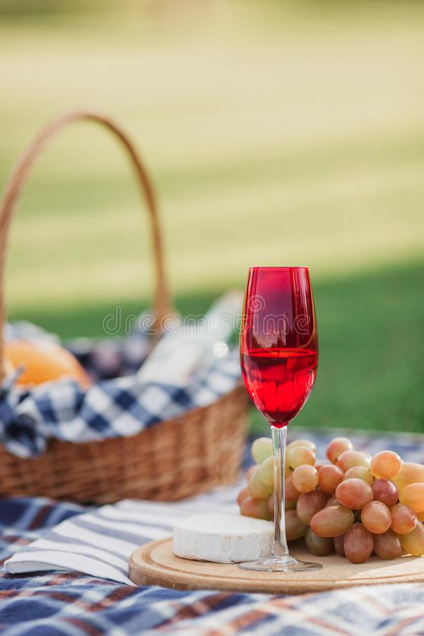 Picnic basket with drinks, food and fruit on green grass outside in summer park royalty free stock photography