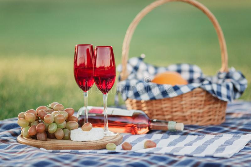 Picnic basket with drinks, food and fruit on green grass outside in summer park stock photo