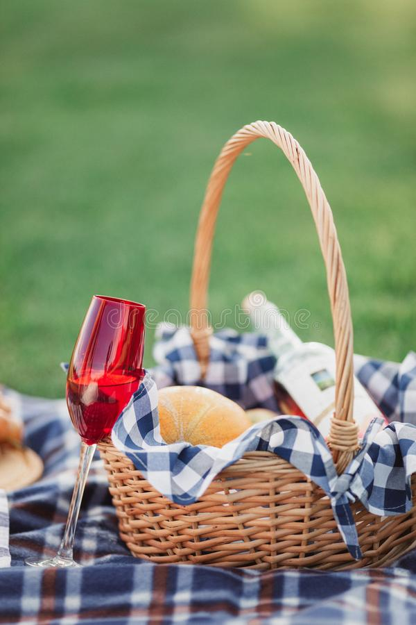 Picnic basket with drinks, food and fruit on green grass outside in summer park stock images