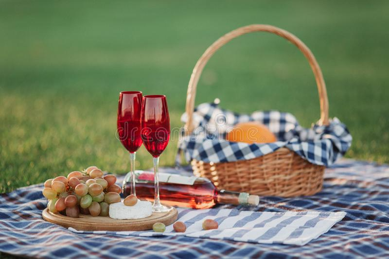 Picnic basket with drinks, food and fruit on green grass outside in summer park. Picnic theme. Summer pastime concept royalty free stock images