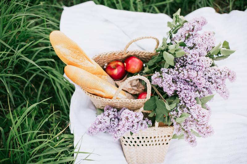 Picnic basket with drinks, fruits and flowers on green grass outside in spring park royalty free stock photo