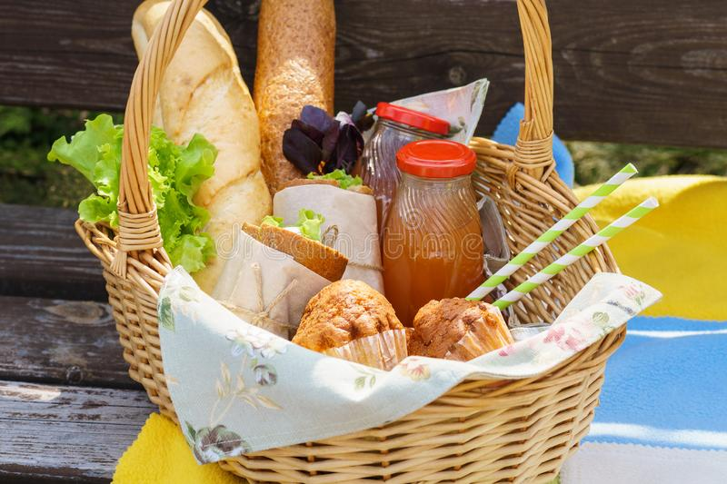 Picnic basket with food and drinks on a park bench for lunch. Picnic basket with various food and drinks on a park bench for an outdoor lunch royalty free stock photo