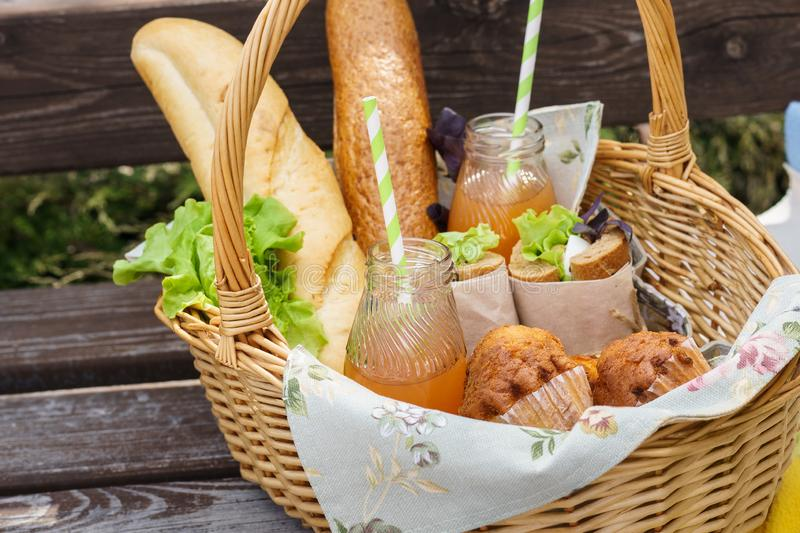 Picnic basket with food and drinks on a park bench for lunch. Picnic basket with various food and drinks on a park bench for an outdoor lunch stock photo