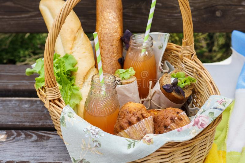 Picnic basket with food and drinks on a park bench for lunch. Picnic basket with various food and drinks on a park bench for an outdoor lunch royalty free stock images