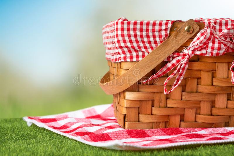 Picnic basket on green grass with tablecloth. relaxing on a picnic, and enjoyable in nature, with space.  stock photography