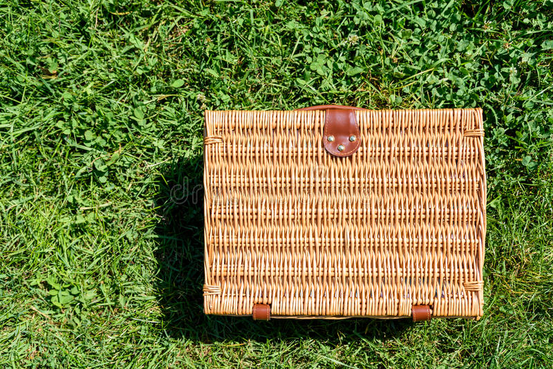 Picnic Basket Hamper In Green Grass. Picnic Basket Hamper With Leather Handle In Green Grass royalty free stock photography