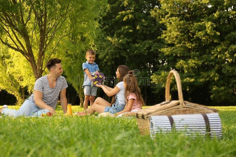 Picnic basket and happy family on  in park. Picnic basket and happy family on background in park royalty free stock images