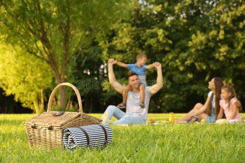 Picnic basket and happy family on background royalty free stock photography