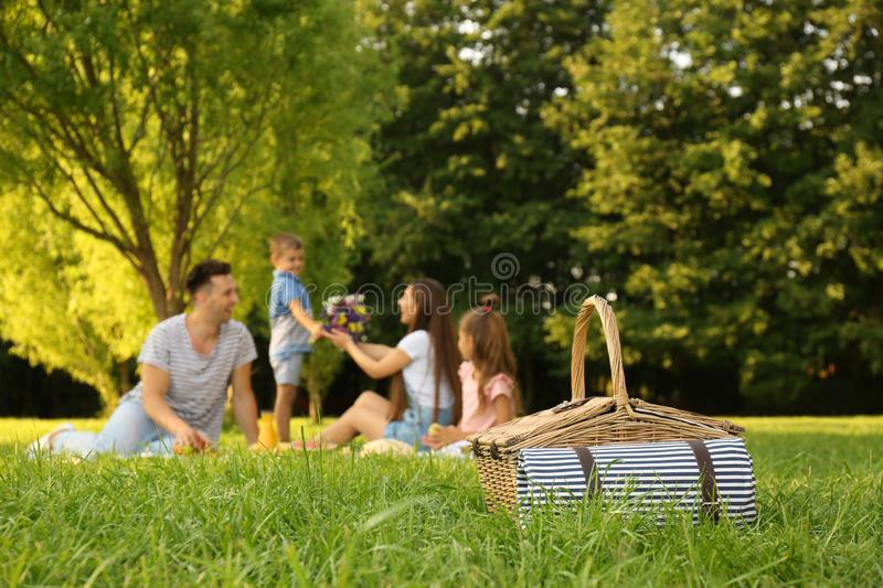 Picnic basket and happy family on background royalty free stock photo