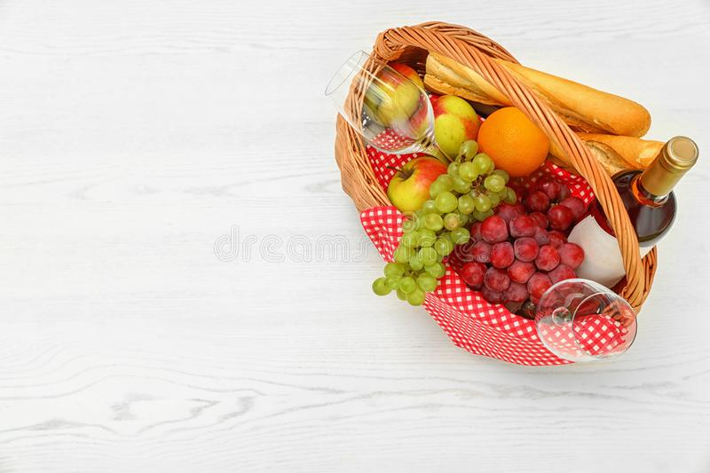 Picnic basket with products and wine on white wooden table, top view stock images