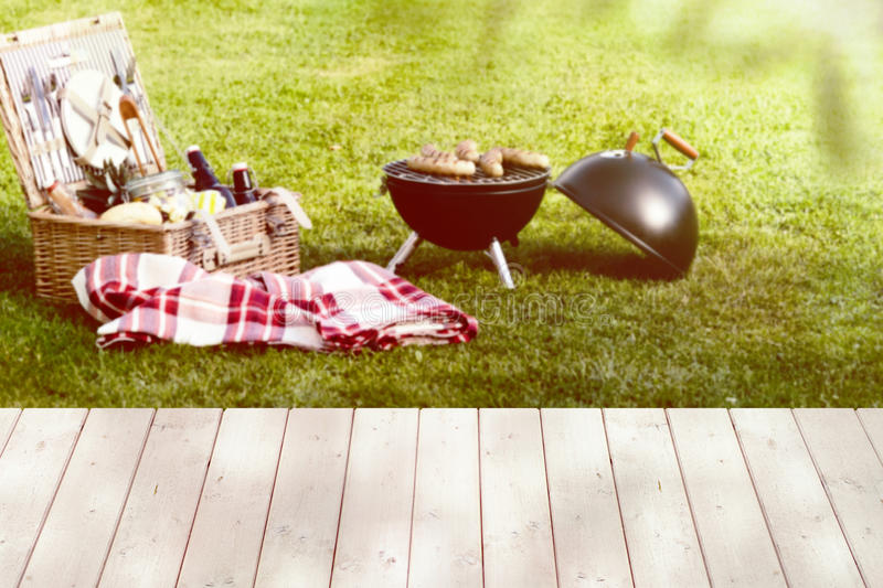 Picnic basket and a round barbecue grill on lawn. Open picnic basket near a folded red checkered tablecloth and a round barbecue grill on the green lawn stock photos