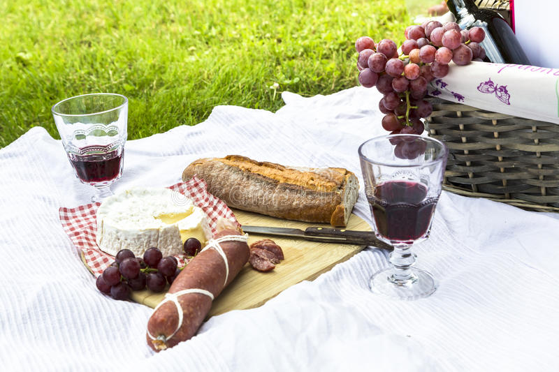 Picnic basket, salami, cheese, baguette, wine and grapes on blanket royalty free stock image