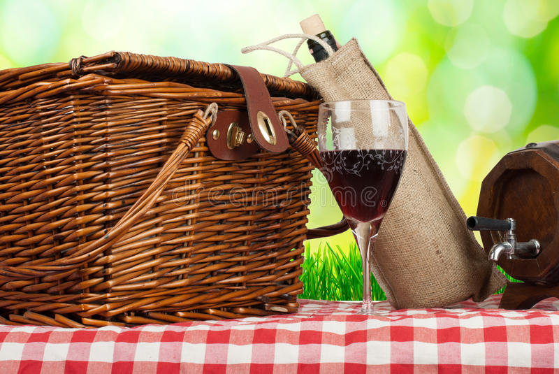 Picnic basket on the table with glass of wine.  royalty free stock images