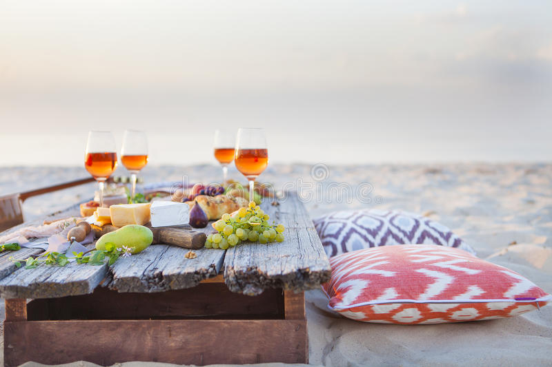Picnic on the beach at sunset in boho style, food and drink conc royalty free stock images