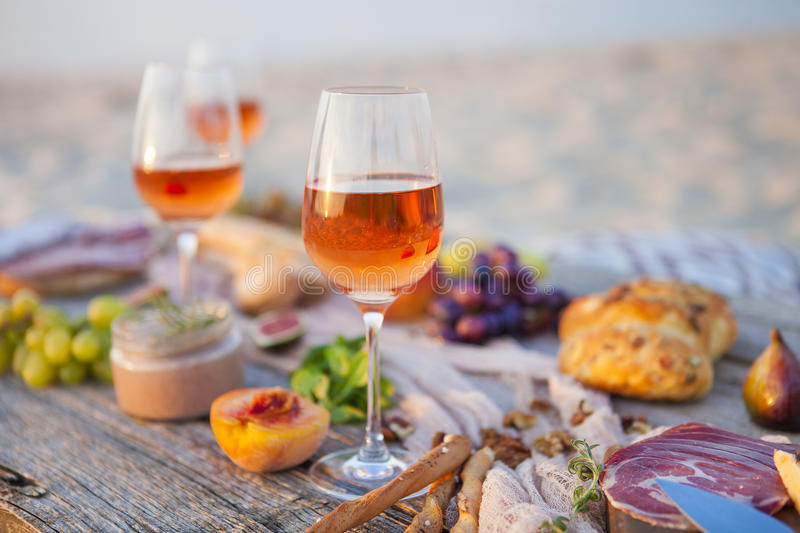 Picnic on the beach at sunset in boho style, food and drink conc stock photos