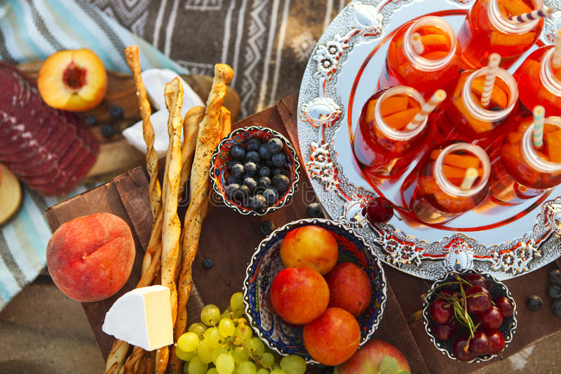 Picnic on the beach at sunset. With fruits and juices in the style of boho stock photo