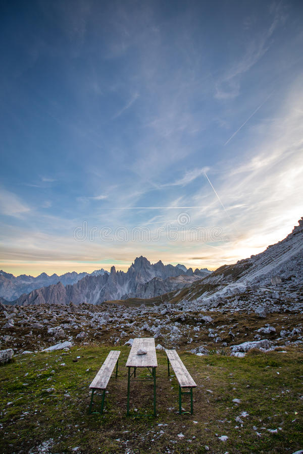Picnic bench in stunning alpine scenery at sunset. The mountain royalty free stock photo