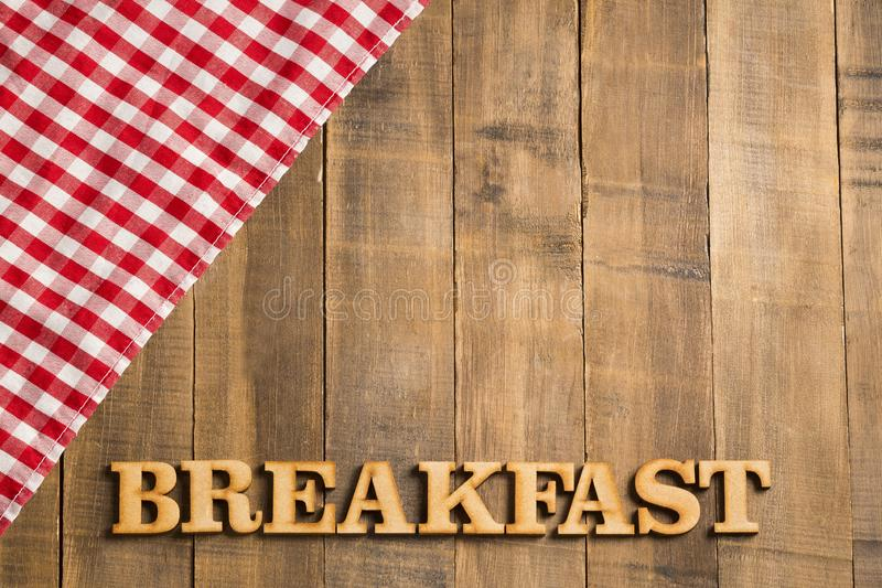 Picnic breakfast - Checkered red napkin and wooden letters. Background for design. Top view stock image