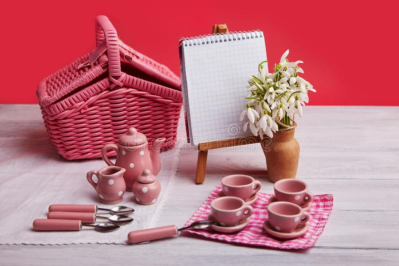 Picnic card with table setting and snowdrops, small essel with blank note pad, silverware, pink and white checkered napkin stock image