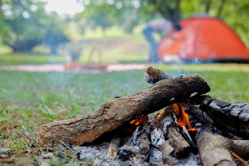 Picnic concept. The fire was burned while picnic with picnic wicker basket on a red and white checked cloth in the field and happy stock images