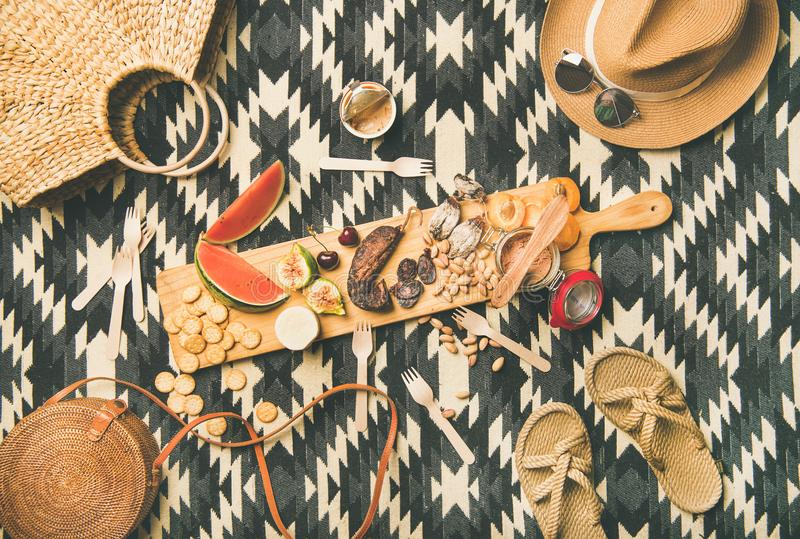 Picnic concept with sausage, fruit, cheese, pate and straw accessories royalty free stock image