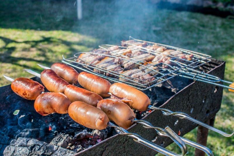 picnic del barbecue delle salsiccie sull'addetto alla brasatura della natura fotografia stock