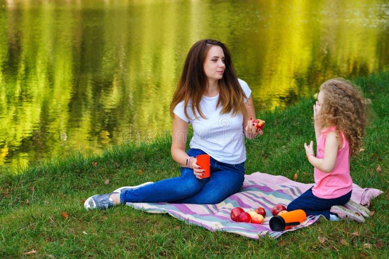 Picnic della famiglia La madre e la figlia si siedono sulla coperta sulle banche del fiume Bambina e madre mangiare frutta Le mel immagine stock
