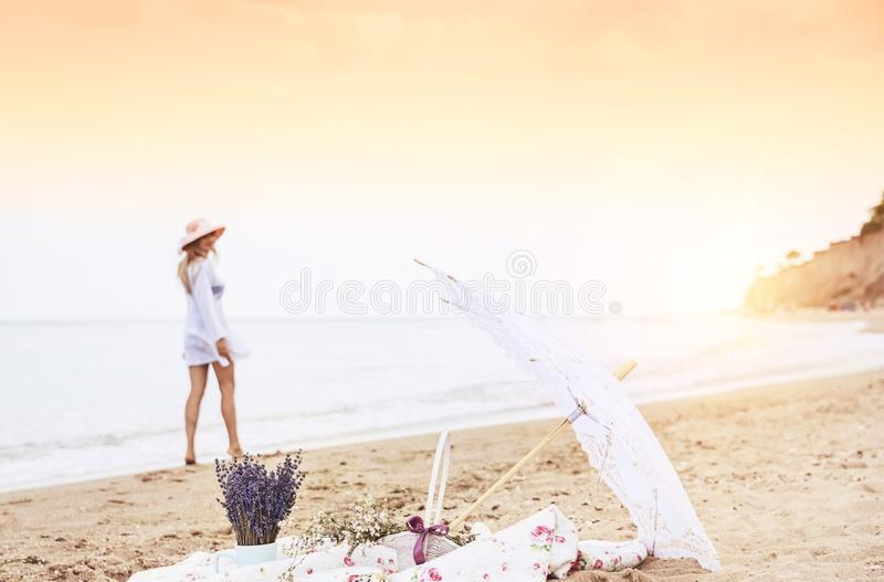 Picnic on a deserted beach and the silhouette of a girl walking along the shore. Vintage retro photo. royalty free stock photo