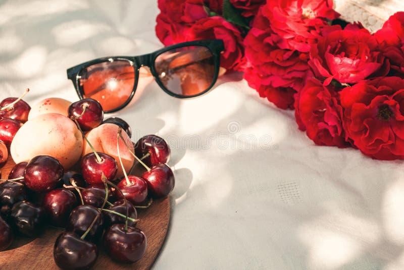 Picnic di estate nel giardino con le rose rosse del giardino in una borsa di vimini, in occhiali da sole e nelle bacche della cil fotografia stock libera da diritti