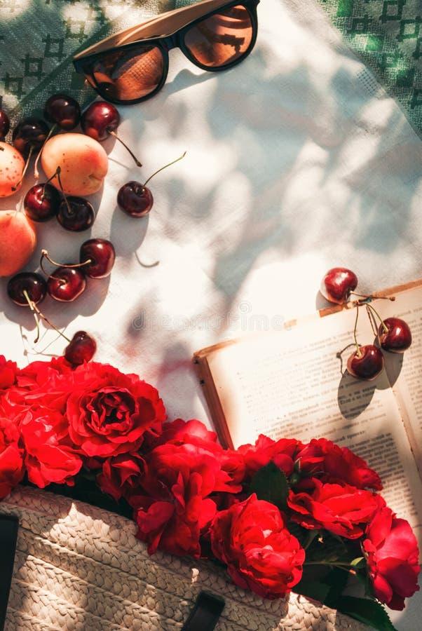 Picnic di estate nel giardino con le rose rosse del giardino in una borsa di vimini, in occhiali da sole e nelle bacche della cil fotografie stock