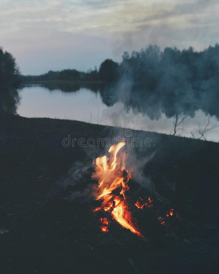 Picnic fire near the river. In summer evening stock photography