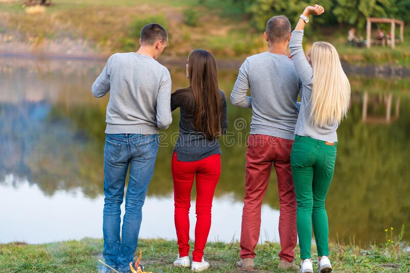 Picnic with friends in at lake near bonfire. Company friends having hike picnic nature background. Hikers relaxing during drink. Time. Summer picnic. Fun time stock photos
