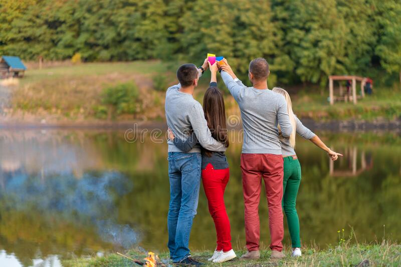 Picnic with friends in at lake near bonfire. Company friends having hike picnic nature background. Hikers relaxing during drink. Time. Summer picnic. Fun time royalty free stock photos