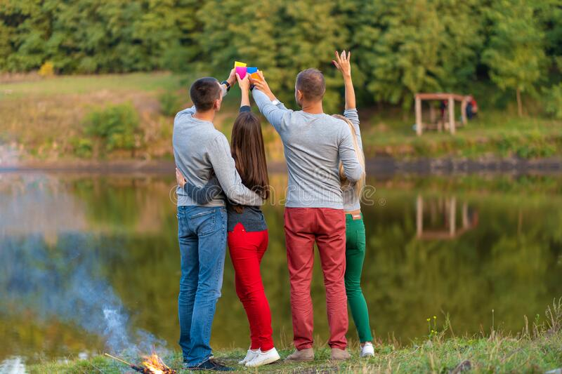 Picnic with friends in at lake near bonfire. Company friends having hike picnic nature background. Hikers relaxing during drink. Time. Summer picnic. Fun time stock photo