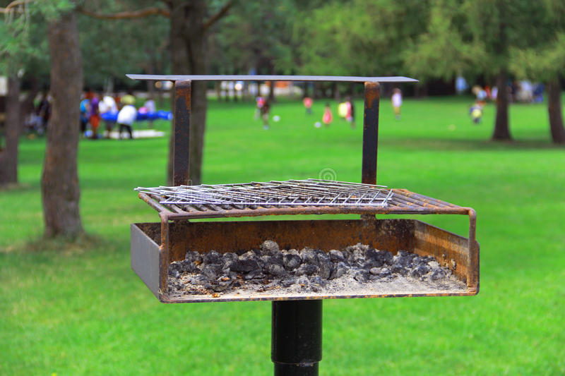 Picnic Grill. With coals and playing people o the background royalty free stock photo