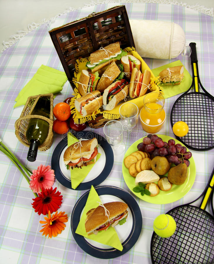 Picnic Hamper. Selection of food for a picnic with a hamper, basket, fruit, wine and tennis racquets royalty free stock photos