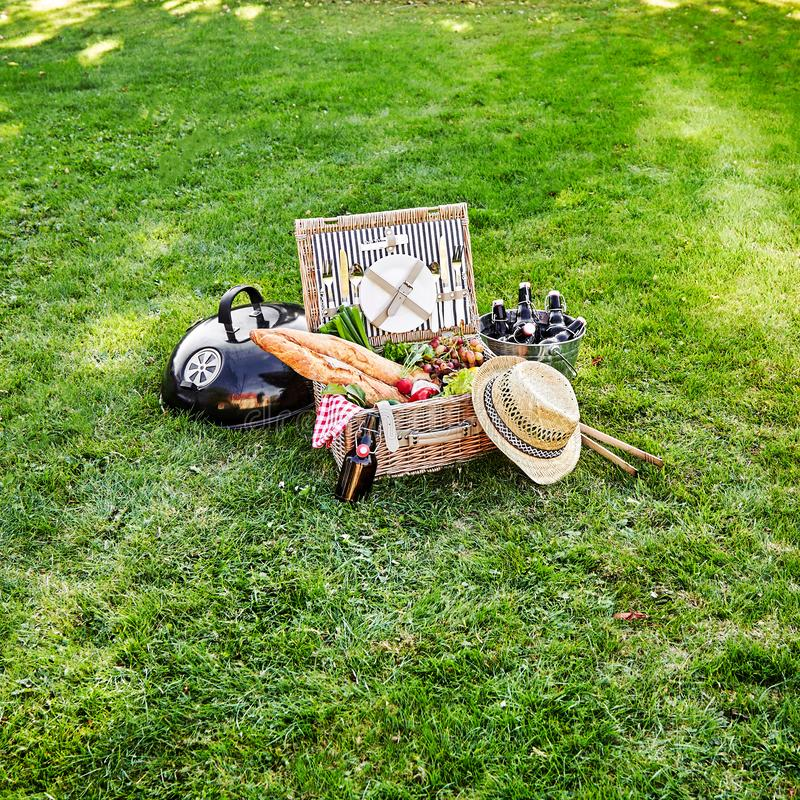 Picnic hamper with fresh vegetables and beer. Vintage style summer picnic hamper with fresh vegetables, bunches of grapes and bottles of beer in a silver cooler stock images
