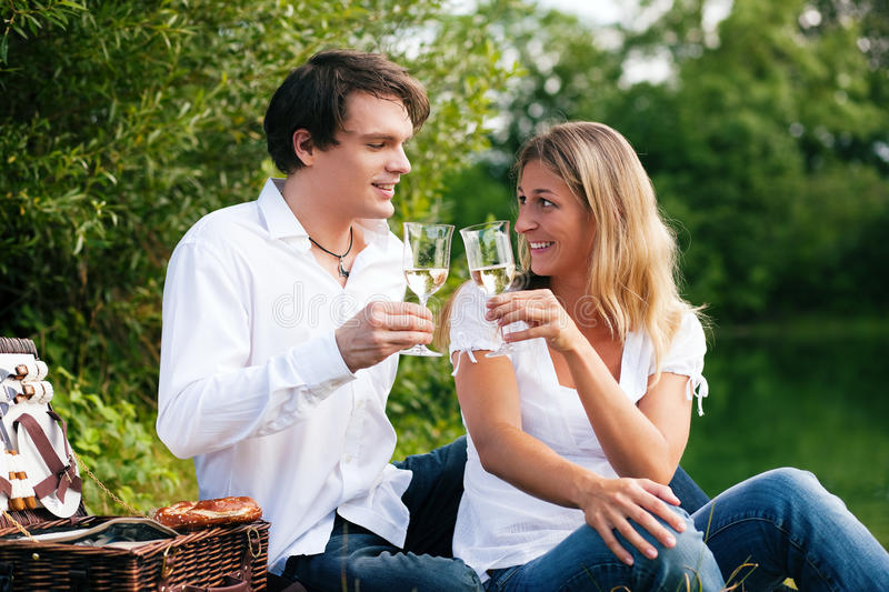 Picnic at the lake with wine. Couple sitting on a lake having a picnic clinking glasses with white wine royalty free stock photo