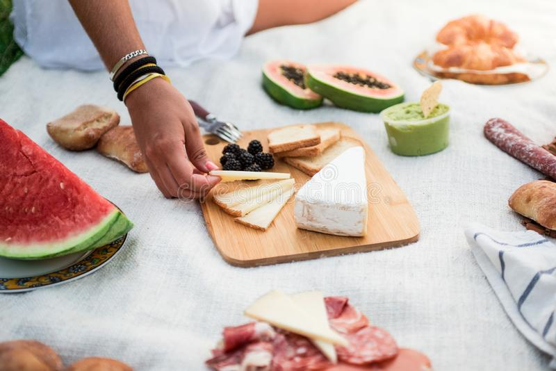 Picnic lunch meal outdoors park. Cheese on cutting board, guacamole, watermelon and a lot of variety of sane food. Hand of a woman taking a piece of cheese royalty free stock photos