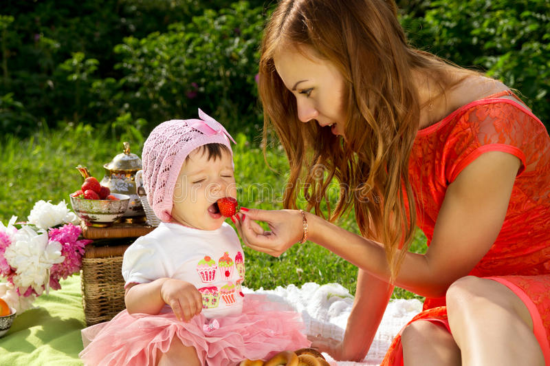 Picnic, mother feeds the child strawberries royalty free stock photography