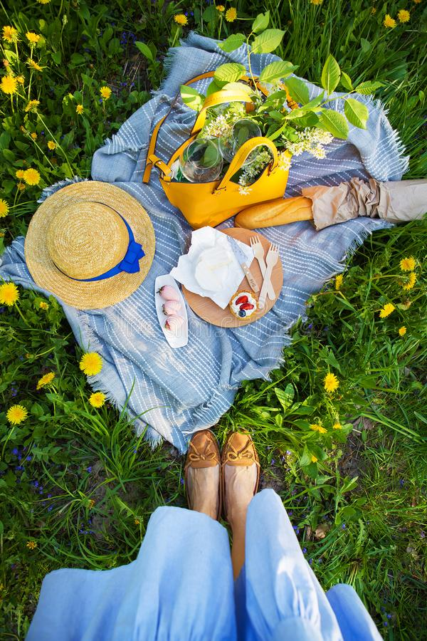 Picnic in nature, plaid on which the food-sire, baguette, cake, strawberry.  stock photo