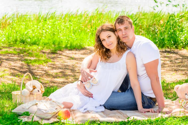 Picnic near the lake, young pregnant couple stock image