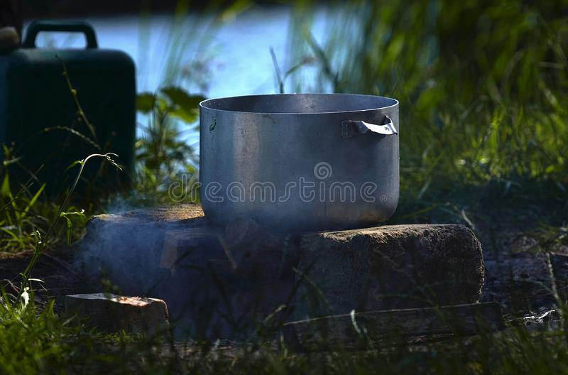 At a picnic near the river, a large metal pan in which fish soup is prepared against the background of green grass and smoke royalty free stock photography