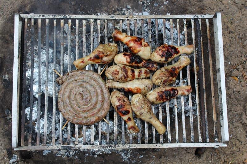 Picnic nella foresta facciamo una griglia con la bacchetta di pollo e la salsiccia casalinga immagini stock