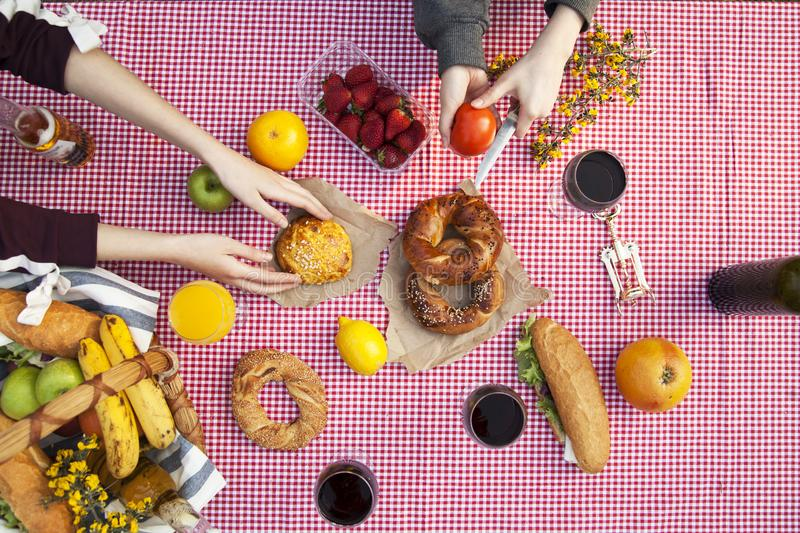 Picnic at the park on the grass: tablecloth, basket, healthy food and accessories, top view stock photos