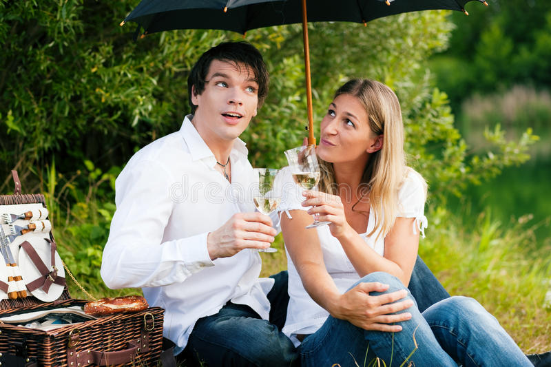 Picnic in the rain with wine. Couple in love sitting on a lake having a picnic with wine - it is starting to rain but they do not care much royalty free stock image