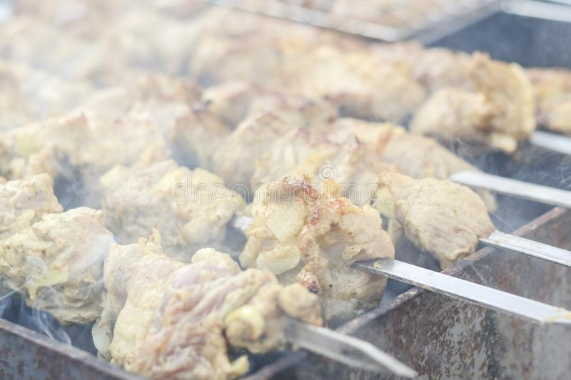 picnic. small grill. on it is cooking kebabs. shallow depth of cut. smoke and frying are real royalty free stock photo