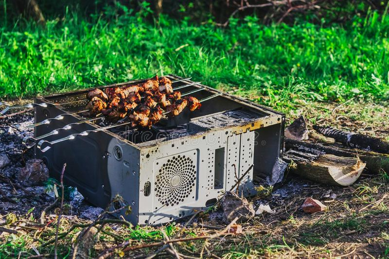 A picnic with a fire and a grill in the old computer case. A picnic IT specialists with a fire and a grill in the old computer case royalty free stock photography